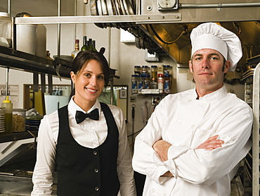 Chef and waitress posing in restaurant kitchen