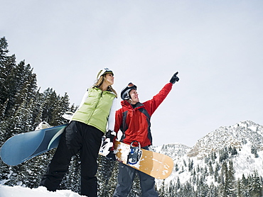 Two snowboarders pointing at sky