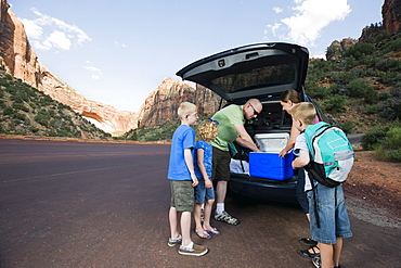 A family on vacation at Red Rock unloading a van