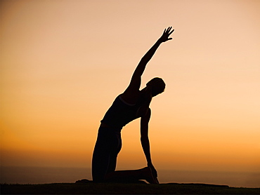 Silhouette of person stretching