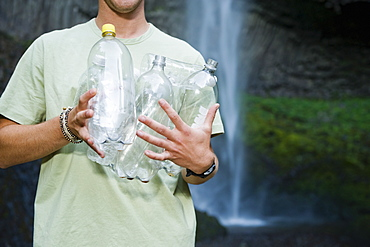 Man holding empty water bottles
