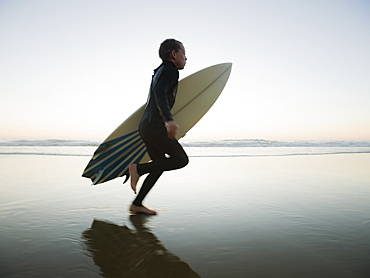 Child running with surfboard