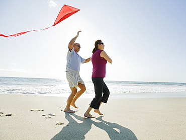 Couple flying kite on beach