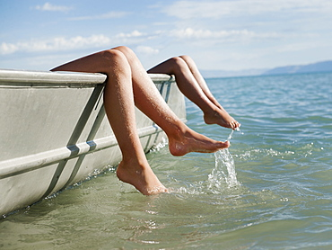 Girls (6-7,8-9) resting on boat