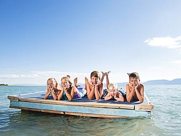Kids (2-3,6-7,8-9,10-11,12-13) playing on raft on lake