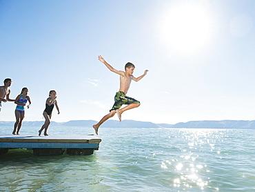 Kids (6-7,8-9,10-11,12-13) playing on raft on lake
