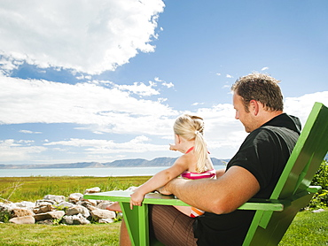 Father and daughter sitting (2-3) on chair and looking at view