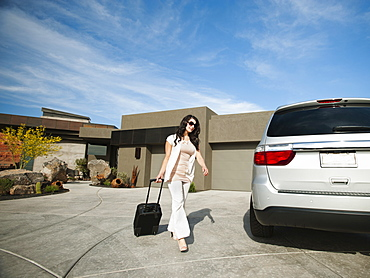 Young woman with suitcase walking towards car, USA, Utah, St. George