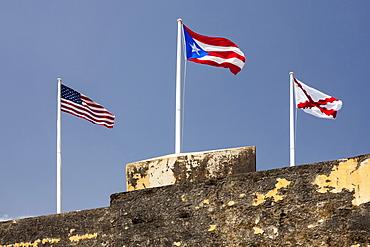 Morro Castle, American, Puerto Rican and naval flags flying against blue sky, El Morro, San Juan, Puerto Rico