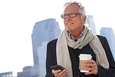 Man in street with coffee and smartphone