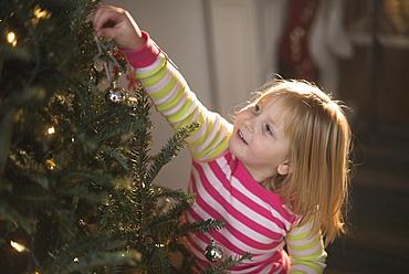 Girl (4-5) decorating christmas tree