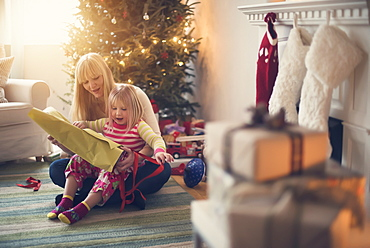 Mother and daughter (4-5) opening christmas presents
