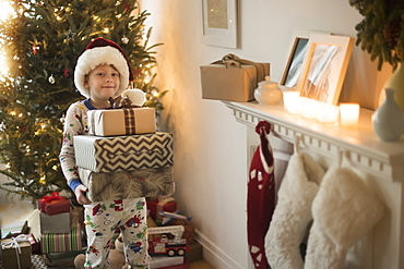 Portrait of boy (6-7) wearing santa claus hat and carrying presents