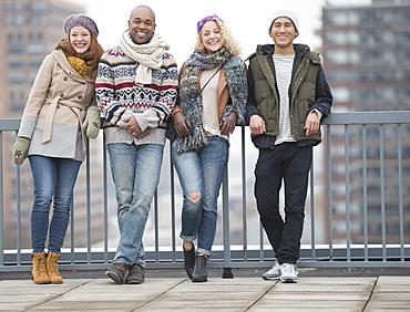 Portrait of happy friends leaning against bridge railing