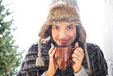 Portrait of young woman wearing winter hat, holding mug