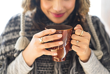 Young woman holding mug with hot drink