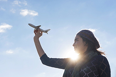 Side view of young woman holding model airplane