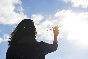 Rear view of young woman holding model airplane against sky
