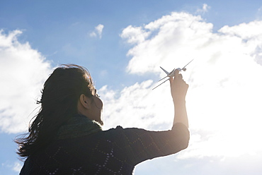Young woman holding model airplane against cloudy sky