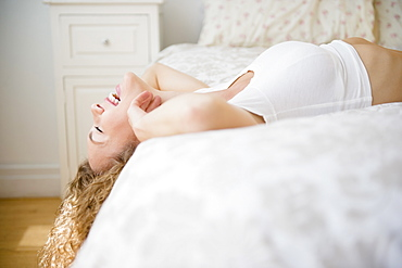Young woman lying down on bed and laughing