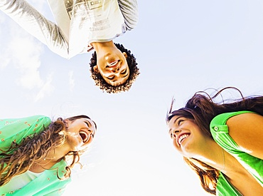 Upward view of friends (14-15) laughing