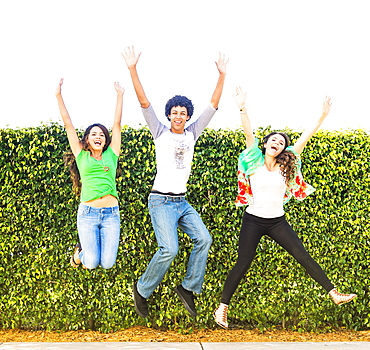 Portrait of friends (14-15) jumping