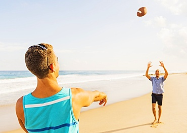 Young men playing football on beach, Jupiter, Florida