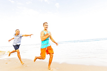 Young men playing with football on beach, Jupiter, Florida