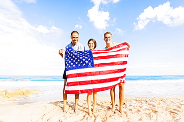 Young people holding American flag on beach, Jupiter, Florida