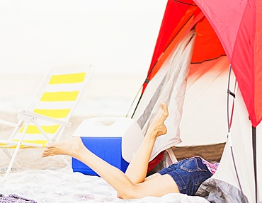 Young woman's legs sticking out from tent