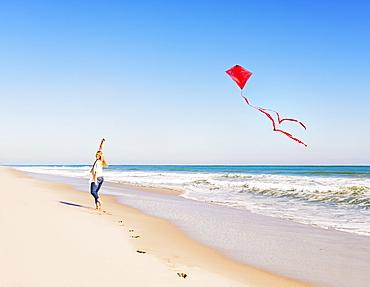 Woman on beach with kite, Jupiter, Florida