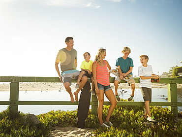Family with three children (6-7, 10-11, 14-15) talking on beach, Laguna Beach, California