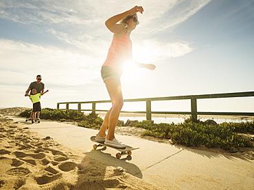 Parents skateboarding with their son (6-7), Laguna Beach, California