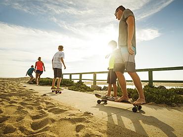 Parents skateboarding with their children (6-7, 10-11, 14-15), Laguna Beach, California