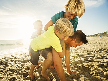 Father playing with his sons (6-7, 10-11, 14-15) on beach, Laguna Beach, California