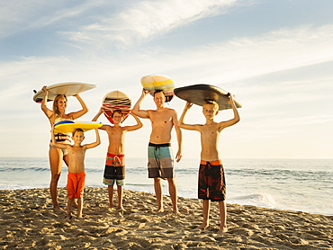 Portrait of family with three children (6-7, 10-11, 14-15) with surfboards on beach, Laguna Beach, California