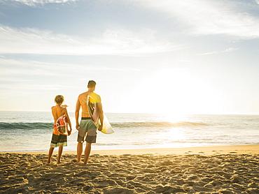 Father and son (14-15) looking at sea, Laguna Beach, California