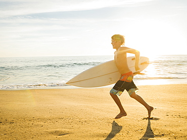 Teenage boy (14-15) with surfboard running on beach, Laguna Beach, California