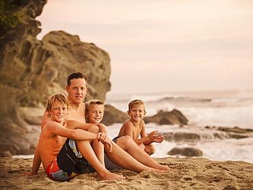 Son with three sons (6-7, 10-11, 14-15) sitting on beach, Laguna Beach, California