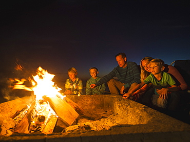 Family with three children (6-7, 10-11, 14-15) cooking marshmallows, Laguna Beach, California