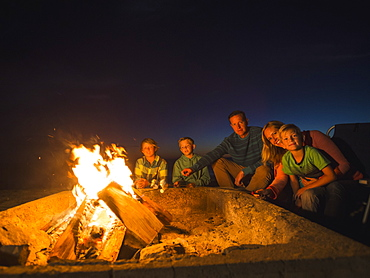 Portrait of family with three children (6-7, 10-11, 14-15) cooking marshmallows, Laguna Beach, California