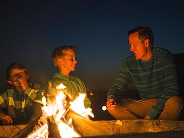 Man talking with his sons (10-11, 14-15) by campfire, Laguna Beach, California