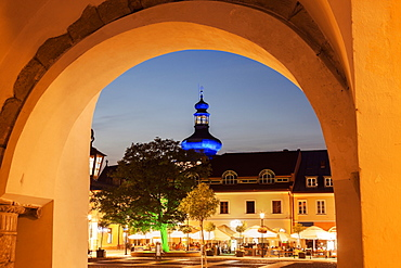 Illuminated Main Square with sidewalk cafe and blue onion dome seen through arch, Poland