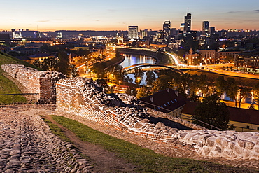 Illuminated riverfront cityscape seen from elevation on opposite bank, Lithuania