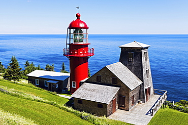 Pointe-a-la-Renommee lighthouse and houses against sea at sunny day, Quebec, Canada