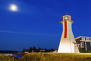 Lighthouse on grassy hill under full moon, Prince Edward Island, New Brunswick, Canada