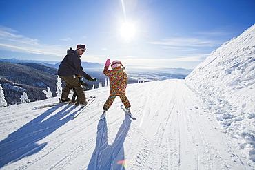 Father skiing with children (6-7, 8-9), Whitefish, Montana USA