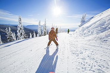 Girl (8-9) skiing in mountains, Whitefish, Montana USA