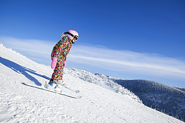 Girl (8-9) skiing in mountains, Whitefish, Montana, USA
