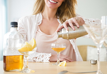Young woman pouring coctail